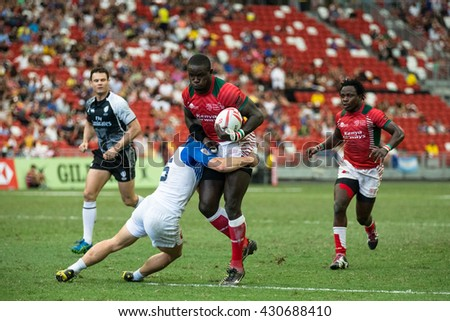 SINGAPORE-APRIL 17:Kenya 7s Team (red) plays against France 7s team (white) during Day 2 of HSBC World Rugby Singapore Sevens on April 17, 2016 at National Stadium in Singapore