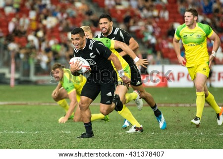 SINGAPORE-APRIL 17:New Zealand 7s Team (black) plays against Australia 7s team (yellow/green) during Day 2 of HSBC World Rugby Singapore Sevens on April 17, 2016 at National Stadium in Singapore