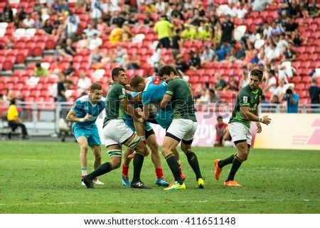 SINGAPORE-APRIL 16: South Africa 7s Team (green) plays against Russia 7s team (blue) during Day 1 of HSBC World Rugby Singapore Sevens on April 16, 2016 at National Stadium in Singapore