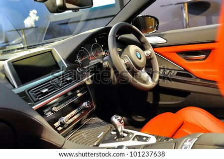 SINGAPORE - APRIL 28: Steering wheel and center console of BMW M6 Convertible at its Preview at Singapore Yacht Show April 28, 2012 in Singapore - stock photo