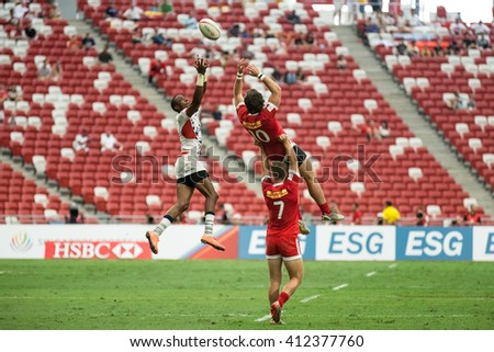 SINGAPORE-APRIL 16: USA 7s Team (white) plays against Canada 7s team (red) during Day 1 of HSBC World Rugby Singapore Sevens on April 16, 2016 at National Stadium in Singapore