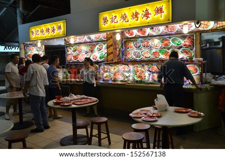 SINGAPORE-AUGUST 31: Customers buy food from hawker center in Singapore on August 31, 2013. Singapore�s hawker food culture has evolved over the years as people love their food and love eating out. - stock photo