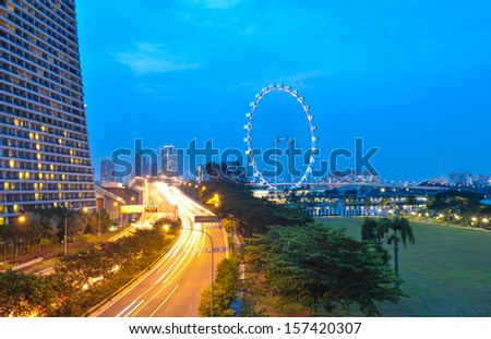SINGAPORE - AUGUST 26: Singapore Flyer and night road on August 21, 2013 in Singapore. Singapore Flyer is the tallest Ferris wheel in the world.