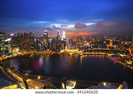 SINGAPORE - CIRCA APR, 2012: Top view of the business district Marina Bay in Singapore at night. Shot from roof Marina Bay Hotel - the world's most expensive standalone casino property at $8 billion. - stock photo