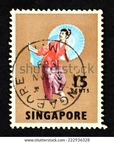 SINGAPORE - CIRCA 1968: Brown color postage stamp printed in Singapore with image of a Malay female dancer in traditional native costume and umbrella.  - stock photo