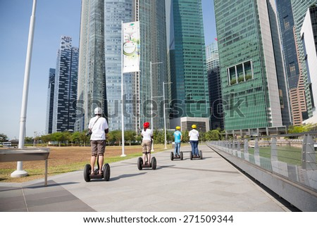 SINGAPORE - CIRCA FEBRUARY 2015: Young people ride on an electric scooter along the waterfront Marina Bay in Singapore. Quay Marina Bay a popular place for walks among the tourists and locals.  - stock photo