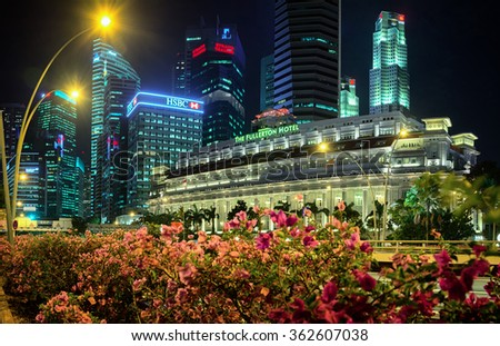 SINGAPORE - CIRCA JAN 2015: Nighttime image of the Fullerton Hotel and other iconic buildings of Singapore's famous skyline, with a brightly lit flower garden in the foreground. - stock photo