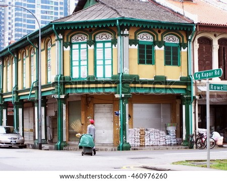 SINGAPORE - CIRCA MARCH 2008: Wooden building on a corner in Chinatown, with a janitor below