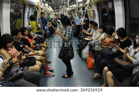SINGAPORE CITY, SINGAPORE - NOV 13, 2013: Rail commuters ride a crowded Mass Rapid Transit (MRT) train through the city centre. Opened in 1987 the MRT has a daily ridership of 2.8 million passengers. - stock photo