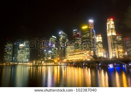 Singapore city skyline at night, overlooking over the waterfront of Marina Bay.