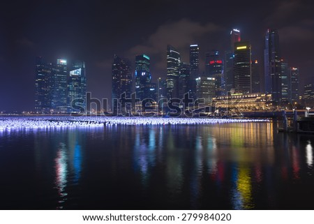 SINGAPORE - 30 DEC 2013: Many lanterns on Marina Bay, with the city's iconic modern skyline lit up in the background, at the annual New Years Eve Celebration. - stock photo