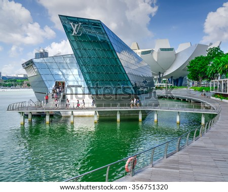SINGAPORE-DEC 30, 2015: People entering the Louis Vuitton store, a luxury shop designed by architect Peter Marino in Marina Bay. LV is founded in 1854 is one of the world leading fashion houses