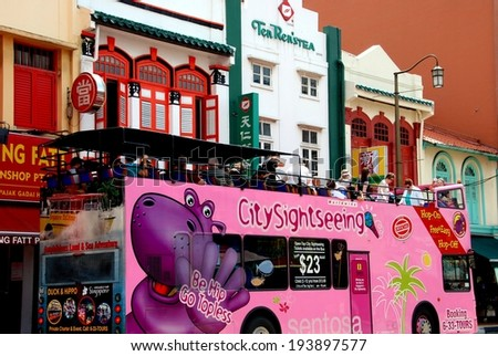 SINGAPORE - December 28, 2007:  A pink City Sightseeing double decker bus with open roof drives tourists past colourful Chinese shops lining South Bridge Road in Chinatown