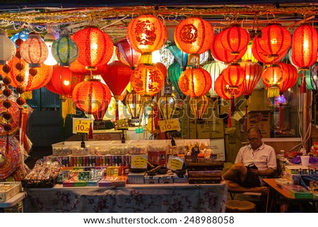 SINGAPORE - DECEMBER 12: A street vendor in Chinatown watches over his store selling Chinese lanterns December 12, 2014. Paper lanterns are popular during Chinese New Year and Mid-Autumn Festivals. - stock photo