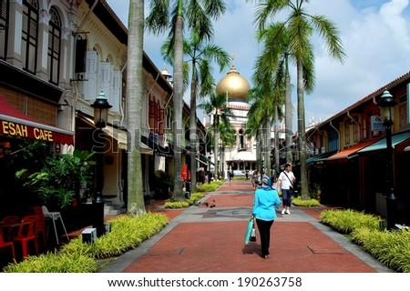 SINGAPORE - December 18, 2007:  Bussorah Street lined with old shop houses offers a fine view of the 1924-28 Masjid Sultan Singapura Mosque in the Kampong Glam historic Arab quarter - stock photo