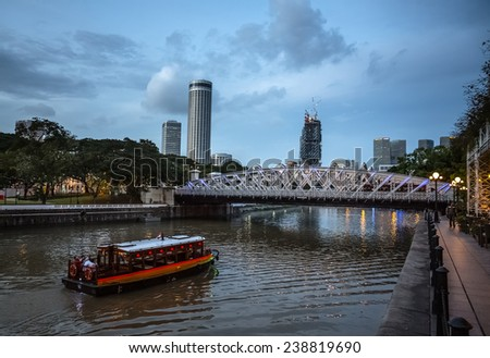 SINGAPORE - DECEMBER 9, 2014: Evening view of the Singapore River. The Singapore River Cruise is a tourist attraction in this former British colony. - stock photo
