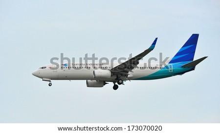 SINGAPORE - DECEMBER 25: Garuda Indonesia Boeing 737-800 landing at Changi Airport on December 25, 2013 in Singapore - stock photo