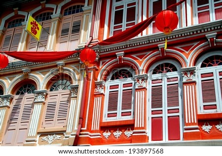 SINGAPORE - December 14, 2007:  Red bunting and Chinese lanterns hang in front of finely restored 19th century shop houses on Temple Street in Chinatown
