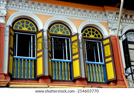 Singapore - December 17, 2007:  Restored early 20th century Chinese shop house  with colorful windows on Bussorah Street in the Kampong Glam Arab district * - stock photo
