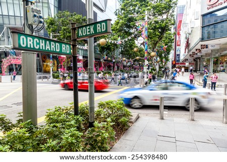 SINGAPORE - DECEMBER 10: Shoppers and tourists walk along Orchard Road and Koek Road during Christmas season Dec. 10, 2014. The area is the city's prime shopping and entertainment district. - stock photo