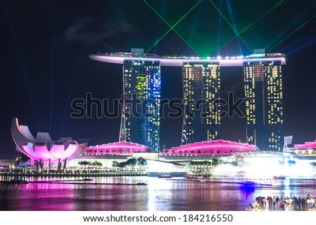 SINGAPORE - DECEMBER 15 2013: The Marina Bay Sands Resort Hotel in Singapore displaying a light show at night. Pink lights. - stock photo