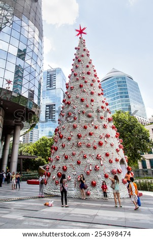 SINGAPORE - DECEMBER 10: Tourists take pictures of a Christmas tree in Orchard Road during the festive season Dec. 10, 2014. The area is the prime shopping and entertainment district of Singapore. - stock photo