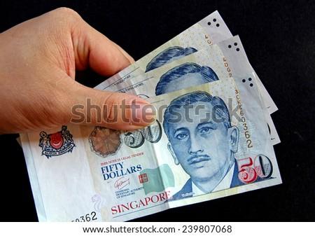 Singapore Dollars banknote money in hand - stock photo