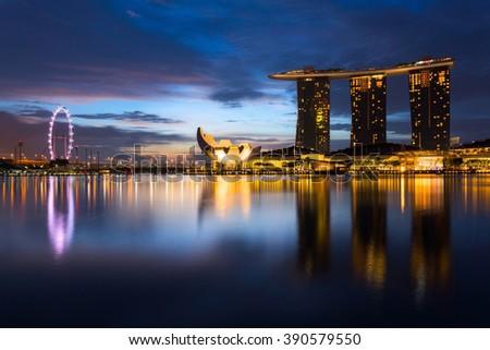SINGAPORE - FEB 24, 2016: Cityscape of Singapore city skyline with Marina Bay Sands hotel and ferris wheel at sunrise in Marina Bay - stock photo