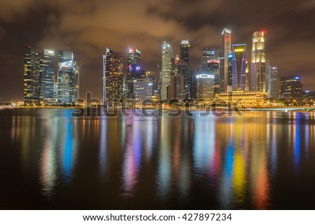 SINGAPORE - FEB 27, 2016: Night scene at Marina Bay Sands. Marina Bay Sand is one of the most famous tourist attraction in Singapore. / Skyline of Singapore at a beautiful sunset - stock photo