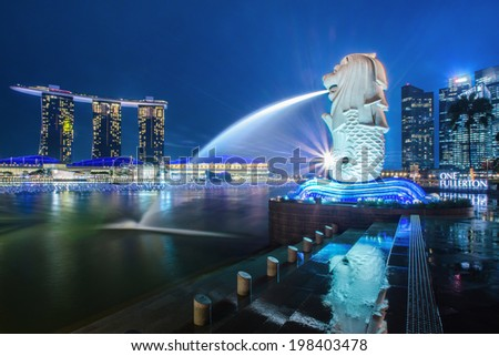 SINGAPORE FEB 12 : The Merlion fountain at night. Feb. 12, 2014 in Singapore. Merlion is an imaginary creature with a head of a lion and the body of a fish and is often seen as a symbol of Singapore. - stock photo