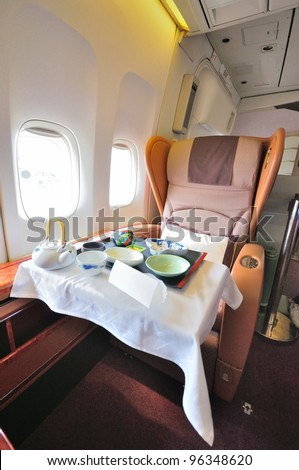 SINGAPORE - FEBRUARY 17: First class cabin seat with dining set on display in Singapore Airlines' (SIA) last Boeing 747-400 aircraft at Singapore Airshow on February 17, 2012 in Singapore - stock photo