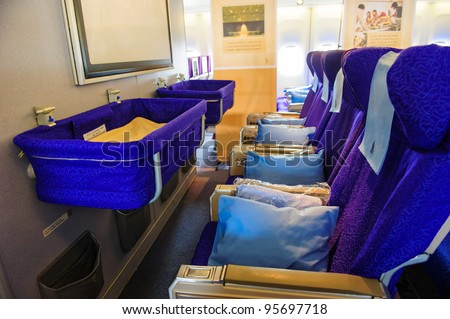 SINGAPORE - FEBRUARY 12: Front row economy class seats with baby bassinet in Singapore Airlines' (SIA) last Boeing 747-400 aircraft at Singapore Airshow February 12, 2012 in Singapore - stock photo