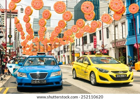 SINGAPORE - FEBRUARY 12, 2015: multicolored taxi cabs driving on South Bridge Road near the corner with Temple Street in Chinatown district with colorful decorations for the upcoming Chinese New Year - stock photo