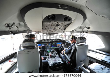 SINGAPORE - FEBRUARY 12: Pilots in the cockpit of Qatar Airways Boeing 787-8 Dreamliner at Singapore Airshow February 12, 2014 in Singapore - stock photo