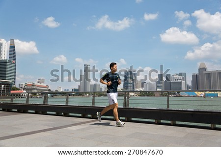 SINGAPORE - FEBRUARY 18, 2015: Young athlete running along the waterfront Marina Bay in Singapore. Quay Marina Bay a popular holiday destination and hanging out with locals and tourists. - stock photo