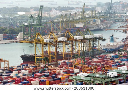 SINGAPORE - 2 JAN, 2014: Commercial port of Singapore. Cargo ships loading and unloading containers in industrial port. One of most important warehouses and trade docks for economy of Asia  - stock photo