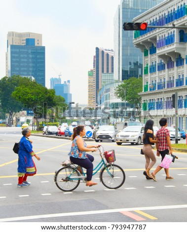 SINGAPORE - JAN 14, 2017: People crossing the road in Singapore. Singapore is a global commerce, finance and transport hub