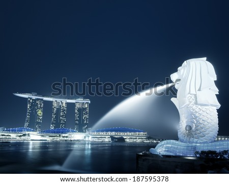 SINGAPORE - JAN 1, 2014: Singapore skyline night panorama. Merlion famous landmark statue of Marina Bay Sands. Waterfront landscape of popular tourist travel destination. - stock photo