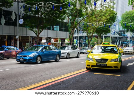 SINGAPORE - 01 JAN 2014: Typical urban traffic, along Orchard Road, a major shopping area in downtown Singapore, during the holidays. - stock photo