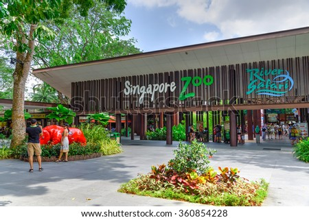 SINGAPORE-JAN 10, 2016: Visitors using smartphone, camera and selfie stick to take photo at the entrance of Singapore Zoo. With 315 species of animal, the zoo attracts 1.7 million visitors each year