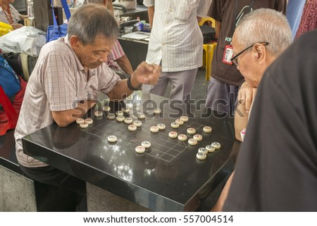 Singapore - January 15, 2017.  Chinatown in Singapore becomes a bustling hive of activity in the build up to Chinese New Year, but locals still find time to play Chinese Chess with friends