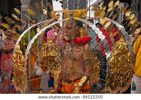 SINGAPORE - JANUARY 30: Elder Hindu devotee carrying a golden kavadi at Thaipusam taken on January 30, 2010 in Singapore. Hindu festival to worship god Muruga. - stock photo