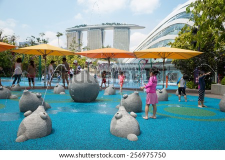 SINGAPORE - JANUARY 27, 2015: Happy children playing on the playground with water attractions in the popular park Gardens by the Bay. Park was opened in 2012 and is a striking sight of Singapore. - stock photo