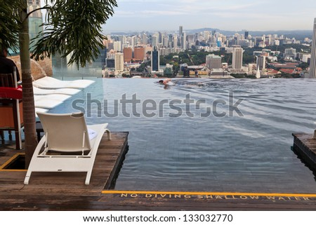 SINGAPORE - JANUARY 5: Infinity swimming pool of the Marina Bay Sands on January 5 , 2013 in Singapore. It is 150m long and set on world's largest cantilevered platform. - stock photo