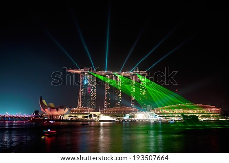 SINGAPORE - JANUARY 23: Marina Bay Sands hotel at night on January 23, 2014 in Singapore. Wonderful show is the largest light and water spectacle in Southeast Asia  - stock photo