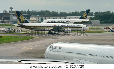 SINGAPORE - JANUARY 10:  Singapore Airlines Boeing 777-200ER passing a fellow Airbus 380 super jumbo at Changi Airport on January 10, 2015 in Singapore - stock photo