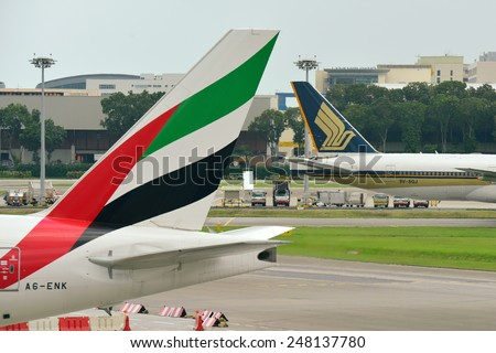 SINGAPORE - JANUARY 10: Tails of Singapore Airlines Boeing 777-200ER and Emirates Boeing 777-300ER at Changi Airport on January 10, 2015 in Singapore - stock photo