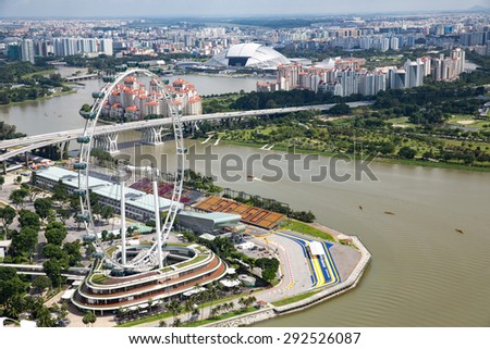 Singapore - January 7, 2015: View of Singapore Flyer ferris wheel from the famous Marina Bay Sands infinity pool.