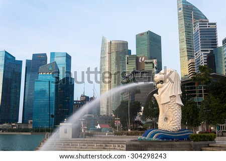 SINGAPORE, JUL 16 2015 :  View of Merilon Statue at Marina Bay in Singapore with tourists and Singapore Skyline in background.