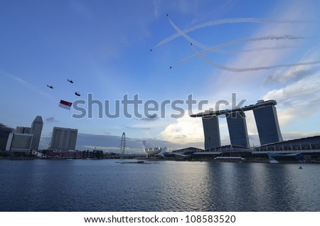 SINGAPORE - JULY 21: helicopter flying Singapore national flag at National Day Parade Singapore 2012 Combined Rehearsal on July 21, 2012 in Singapore. - stock photo